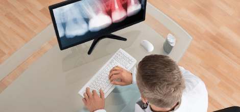 Dentist looking at an X-Ray on a computer screen