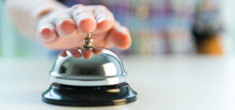 Hand ringing hotel bell for attention